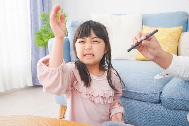 child waves away vape smoke